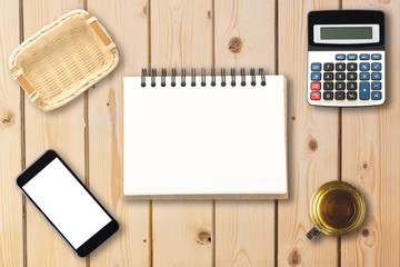 Top view of open spiral blank notebook with smartphone, calculator, empty bamboo basket, and cup of tea on wooden desk background for office business concept