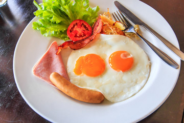American breakfast; Fried eggs, sausages, ham and fresh salad