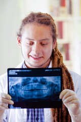 Young doctor with long dread locks posing for camera, holding up x ray image staring at it, clinic in background, medical concept