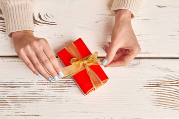 Wall Mural - Well-groomed female hands with a red gift on a wooden background.