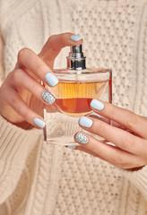 Wall Mural - Beautiful perfume bottle in woman's hands.