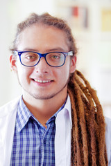 Young doctor with long dread locks posing for camera while smiling, clinic in background, medical concept