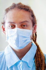Young doctor with long dread locks posing for camera, wearing facial mask covering mouth, clinic in background, medical concept