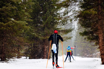 group skiers athletes in pine forest snowfall skiing competitions
