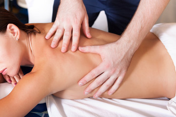 Therapist doing healing treatment on woman back. Chiropractic, osteopathy.