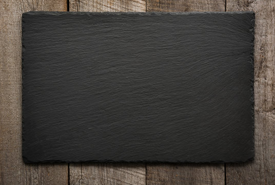 Black slate tile on wooden background. Top view.