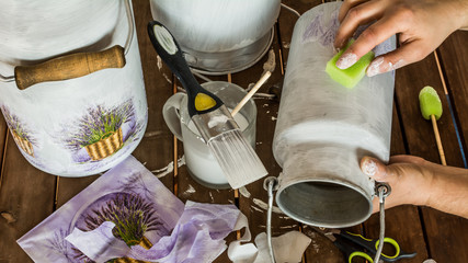 Decorating old milk churns with lavender pattern - decoupage accessories (brush, scissors, tissues, sponge, paint) and hands of an artist on a table. High angle view.