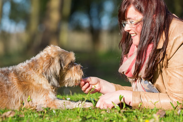 young woman gives her dog a treat