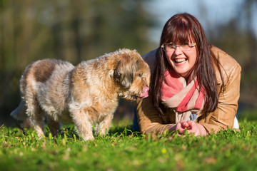 young woman lies with her dog in the grass