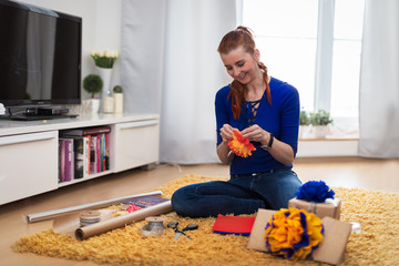 Smiling woman sitting on the floor decorating presents.