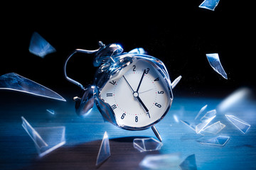 broken alarm clock with shattered glass on a dark background