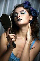 Donna Vintage si guarda allo specchio il suo trucco coloratissimo