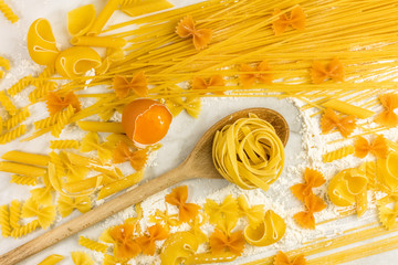 Various types of pasta on marble with egg