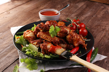barbecue chicken wings close up on wooden tray with red spice sauce and salad