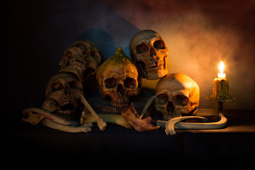Pile of skulls and bones on wooden plate in dim light with candlelight