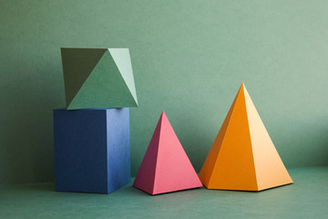 Abstract geometrical solid figures still life. Colorful three-dimensional pyramid prism rectangular cube arranged on green background. Yellow blue pink malachite colored objects textured paper surface Fotoväggar