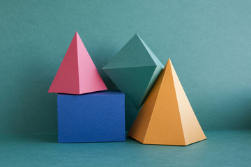 Colorful abstract geometric background with three-dimensional solid figures. Pyramid prism...