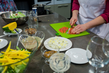 The chef prepares a salad with salmon