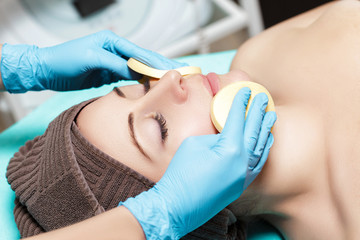 doctor beautician cleanses skin woman with sponge. cosmetology treatment skincare face. Spa procedures