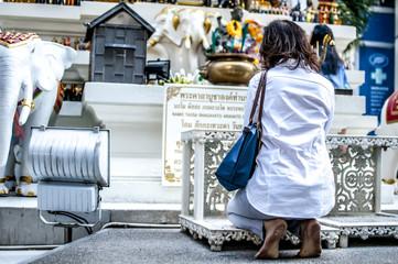 fedele prega davanti un tempio per strada in Thailandia