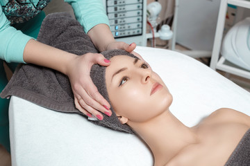 beautician prepares patient for Spa procedures in Spa salon. young woman with towel on head
