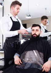 Smiling man forming beard of client into shape