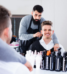 Male hairdresser preparing client for haircut