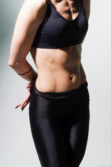 Slim woman belly against a light background.