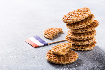 Mini stroopwafel, syrupwaffles cookies and Netherlands national flag light gray background with copy space.