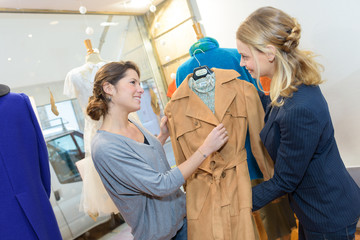 sales assistant showing coat to customer in a clothes shop