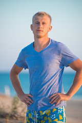 Young blond guy in a blue T-shirt and shorts stands on the background of the sea