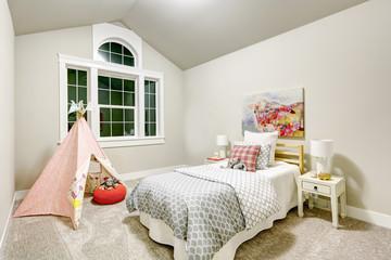 Light grey girl's bedroom features vaulted ceiling
