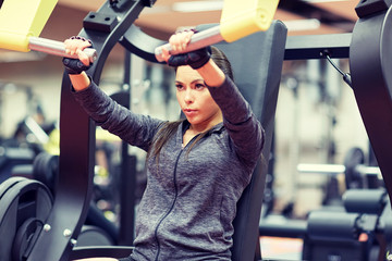 woman flexing muscles on chest press gym machine