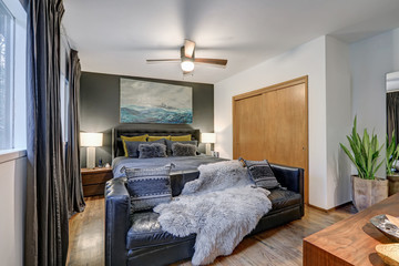 Masculine bedroom features gray accent wall