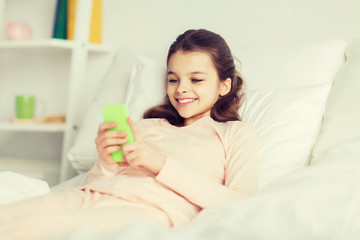 happy girl lying in bed with smartphone at home
