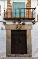 Ancient door with feudal coat of arms on the lintel. Old town of Orgaz. Spain.