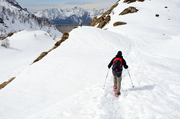 Hiker with snowshoes in winter mountains, Alps, Italy