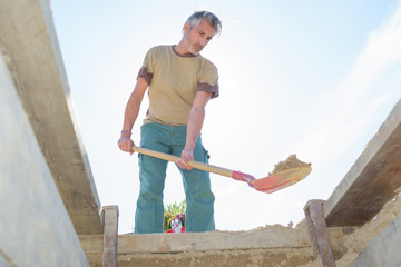 man using a spade to dig