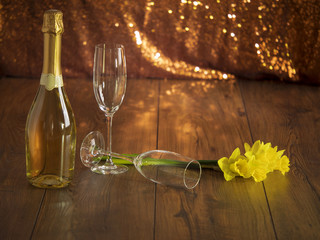 Bottle of champagne two glasses and bunch of daffodils on a wooden surface.