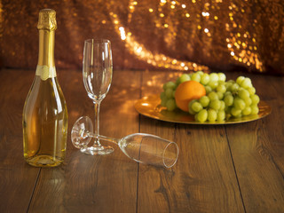 Still life: Bottle of champagne flutes and plate with fruits.