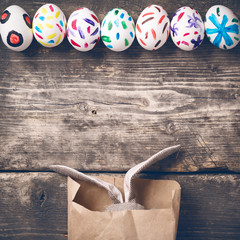 Easter bunny in a paper bag on old boards. Rabbit. Old board background. Easter ideas. Easter eggs. Space for text. Image in trendy toning.
