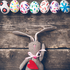 Easter bunny on old boards. Old board background. Rabbit. Easter ideas. Easter eggs. Space for text. Image in trendy toning. On the heart text happy Easter.