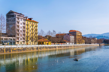 historical buildings stretched along riverside of dora riparia river in the italian city torino.