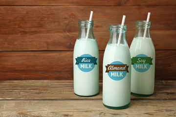 Three bottles of milk with straws on wooden background