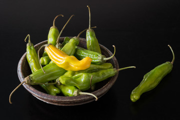Fresh Shishito peppers in pottery bowl