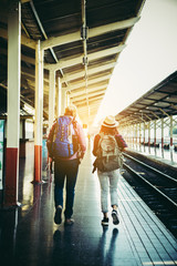 Young attractive hipster couple waiting for the train to go traveling. Travel concept.