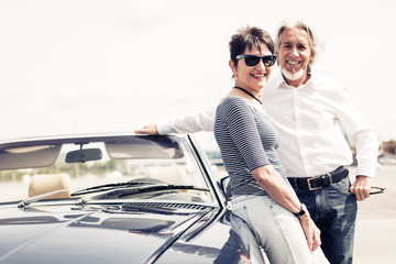 Senior Couple Standing Next To Convertible Classic Car