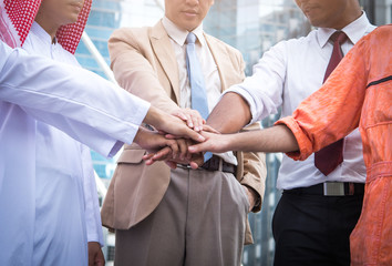 arab businessman and Engineer/architect stacking hands express their teamwork and cooperation, Business People Collaboration Teamwork Union Concept.