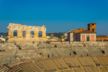 facades of several buildings emerge behind the roman arena in the italian city verona