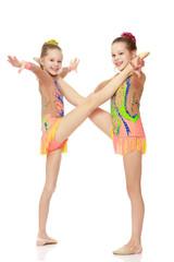 Two girls gymnast sitting on splits.